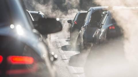 Nahaufnahme von Autos im stockenden Verkehr und Abgaswolken.