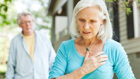 Lungenembolie: Eine ältere Frau steht im Garten und hält eine Hand an ihren Brustkorb. Im Hintergrund steht ihr Mann, beide scheinen erschrocken.