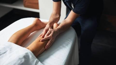 Ein Physiotherapeut massiert die Beine einer Patientin, damit die gestaute Lymphe abfließen kann.