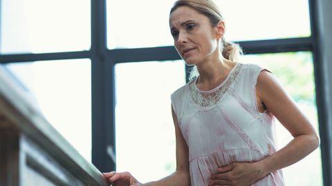 Magengeschwür: Eine Frau steht in ihrer Wohnung und hält sich den Bauch. Sie wirkt angespannt und als hätte sie Schmerzen.