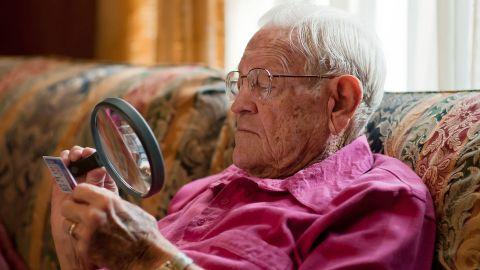 Ein älterer Mann sitzt auf einem Sessel. Er hält eine große Lupe in der Hand und blickt durch sie auf eine Plastikkarte.