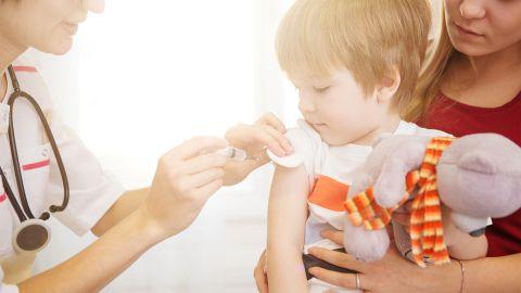 Masern: Ein Kind sitzt auf dem Schoß der Mutter und bekommt von einer Kinderärztin eine Impfung in den Oberarm.