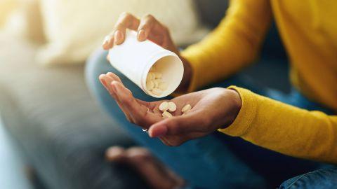 Nahaufname: Eine junge Frau schüttet mehrere Tabletten aus einer größeren Medikamentendose in ihre offene Hand.