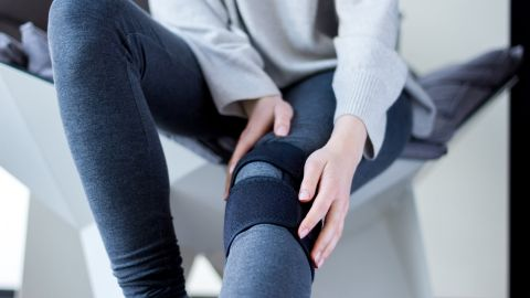 Meniskusriss: Eine Frau sitzt auf einem Stuhl, ihr linkes Bein ist ausgestreckt. Um ihr linkes Knie ist eine Stützbandage gebunden.