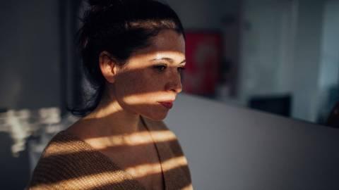 Eine Frau sitzt mit stumpfem und in sich gekehrtem Blick im Halbdunkeln.