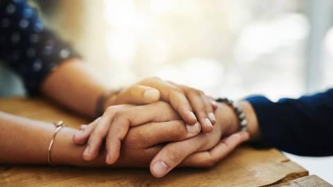 Eine Person hält über den Tisch hinweg tröstend die Hand einer anderen Person in ihren beiden Händen.