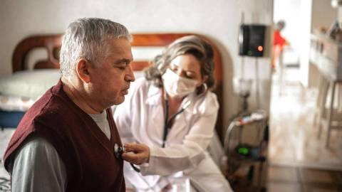 Ein älterer Mann sitzt auf einem Krankenbett. Sein Gesichtsausdruck deutet auf körperliche Schwäche hin. Eine Ärztin mit Mundschutz hört sein Herz mit dem Stethoskop ab.