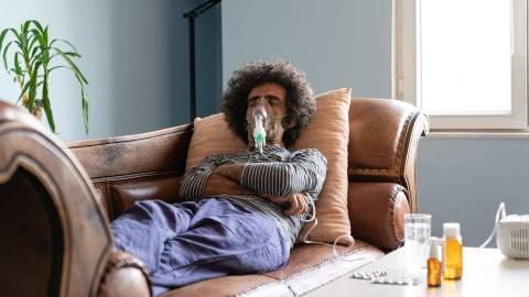 Ein Mann liegt auf dem Sofa. Er ist über eine Maske an ein Beatmungsgerät angeschlossen. Auf dem Tisch neben ihm stehen Medikamente.