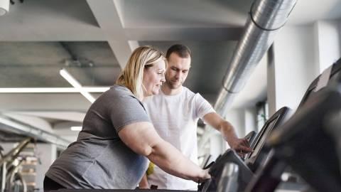 Ein Mitarbeiter eines Fitnessstudios zeigt einer Frau mit starkem Übergewicht, wie das Laufband funktioniert.