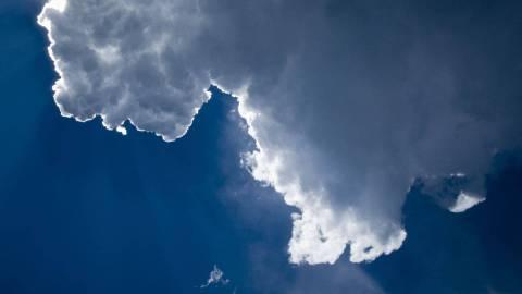 Der blaue Himmel wird von einer weißen Wolke verdeckt, hinter der die Sonne hervorscheint.