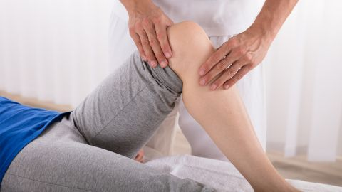 Patellaluxation: Eine junge Frau liegt auf einer medizinischen Liege. Ein Physiotherapeut tastet mit beiden Händen ihr gebeugtes Knie ab.
