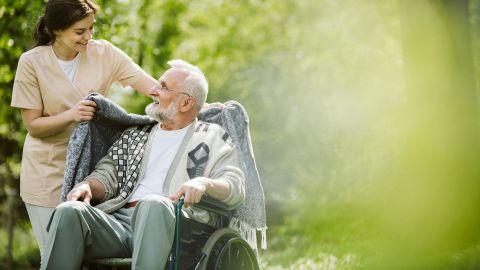 Teilstationäre Pflege: Eine junge Pflegerin steht neben einem älteren Mann, der im Rollstuhl sitzt. Sie legt dem Mann eine Strickjacke um beide Schultern.