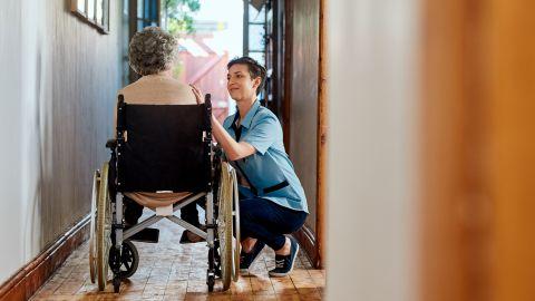 Pflege von zu Hause: Eine alte Dame im Rollstuhl steht im Hausflur auf dem Weg nach draußen. Ihre häusliche Pflegerin spricht mit ihr und hockt dabei neben der Dame, um mit ihr auf Augenhöhe zu sein.