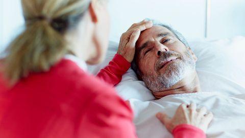 Leistungen für schwer kranke und sterbende Menschen: Ein Mann mittleren Alters liegt in einem Krankenbett. Er schaut leicht zur Seite an den Bettrand. Dort sitzt eine Frau. Mit ihrer linken Hand berührt sie die Stirn des Mannes.