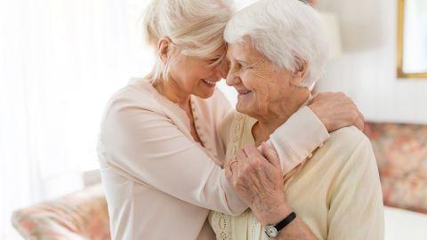 Pflegeversicherung – Hilfe für pflegende Angehörige: Mutter und Tochter stehen sich gegenüber und lachen. Die Tochter legt ihren Arm um die rechte Schulter der Seniorin. Sie wiederrum hält sich mit einer Hand am Arm der jüngeren Frau fest.