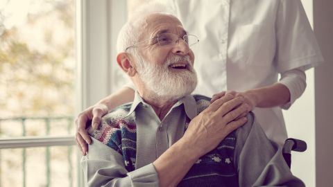 Pflegebegutachtung: Ein älterer Mann mit Bart und Brille, der im Rollstuhl sitzt, wendet sich lächelnd nach hinten zu einer Person in weiß, die hinter ihm steht und ihm die Hände auf die Schultern legt.