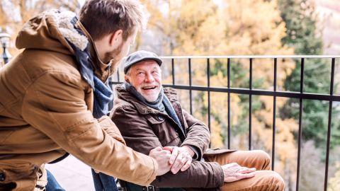 Ein im Rollstuhl sitzender älterer Mann und ein jüngere Mann bei einem Spaziergang. Der jüngere Mann stützt sich auf die Lehne des Rollstuhls, lehnt sich in Richtung des älteren Mannes und legt die Hand auf dessen Arm.