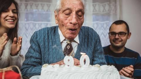 Prävention in Pflegeeinrichtungen: Ein festlich gekleideter älterer Herr pustet die Kerze einer Geburtstagstorte aus, die mit der Zahl 90 geschmückt ist. Zwei jüngere Menschen stehen um ihn herum, lächeln und applaudieren.