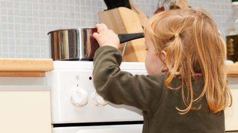 Ein kleines Mädchen steht vor einem Küchenherd auf dem ein Topf mit kochendem Inhalt steht und greift an den Topfrand, um in den Topf rein zu schauen.