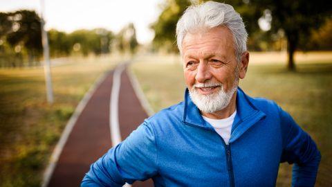 Prostatasteine: Ein älterer Herr steht in einem Park, im Hintergrund ist ein Weg zu sehen. Er trägt Sportkleidung und wirkt fit und zufrieden.