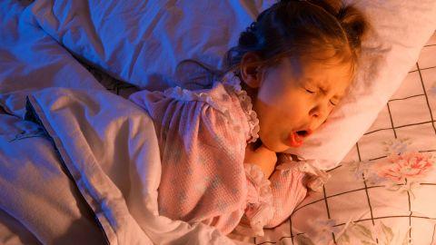 Pseudokrupp: Ein kleines Mädchen liegt in einem Bett. Sie hat sich leicht auf die Seite gedreht, den Mund weit geöffnet und hustet stark.