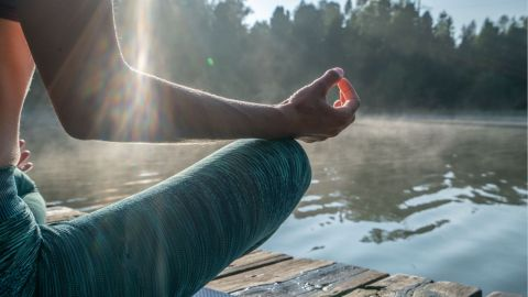 Ein Mann sitzt im Schneidersitz auf einem Holzvorsprung an einem See. Seinen rechten Arm hat der Mann angehoben, seine Finger zu einer Mudra geformt. Offenbar mediziert er, eventuell entspannt er beim Yoga.