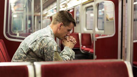 Posttraumatische Belastungsstörung (PTBS): Ein Mann sitzt alleine in einem Zugabteil, stützt den Kopf auf seine Hände und schaut zu Boden. Die Hände hat er ineinander verschränkt.