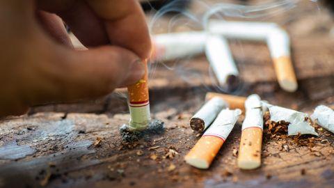 Rauchen: Eine Hand hält eine qualmende Zigarette und drückt sie auf einem hölzernen Untergrund aus. Ringsherum liegen einige Zigarettenstummel.
