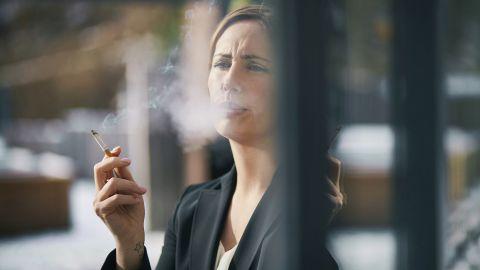 Rauchen: Eine Frau steht an einem Fenster, hält eine Zigarette in der Hand und atmet Rauch aus. Rauchschwaden umgeben ihr Gesicht.