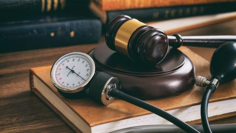 Rechte für Patienten: Ein mechanisches Blutdruckmessgerät liegt zusammen mit einem Richterhammer auf einem großen Buch, welches auf einem Massivholztisch liegt. Im Hintergrund liegen Bücher.