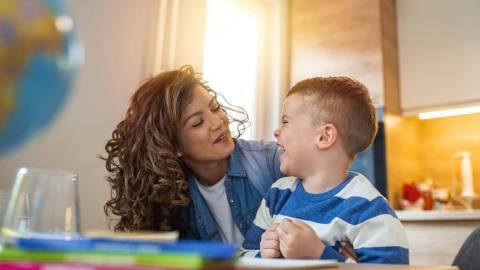 Ein kleiner Junge sitzt am Küchentisch und dreht sich lachend zu einer Frau um, die sich von der Seite zu ihm gebeugt hat und ihn freundlich anblickt.