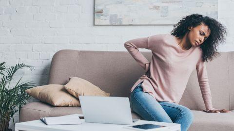 Rückenschmerzen: Eine junge Frau sitzt auf einer Couch und hat ihren Oberkörper leicht zur Seite gebeugt. Mit einem Arm stützt sich die Frau ab, mit der anderen Hand fasst sie sich an den Rücken.