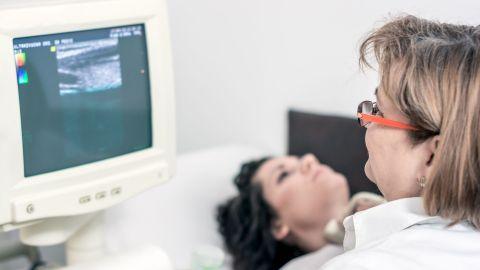 Schilddrüsenkrebs: Eine Patientin liegt auf einer Krankenhausliege. Vor ihr sitzt eine Ärztin und führt eine Ultraschalluntersuchung ihrer Schilddrüse durch. Die Ärztin beobachtet das Ultraschallbild auf einem Monitor.