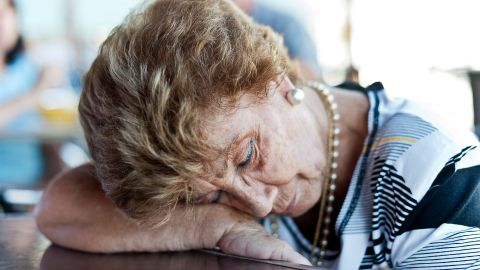 Eine ältere Frau stützt ihren Kopf auf ihren Arm, der auf einem Tisch liegt. Sie scheint zu schlafen.