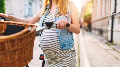 Eine junge hochschwangere Frau schiebt ihr Fahrrad über die Straße. Sie ist sommerlich gekleidet und die Sonne scheint.