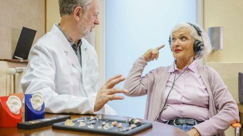 Eine ältere Frau sitzt neben einem Hörgeräte-Akustiker und trägt einen Kopfhörer. Sie schaut den Mann an und gestikuliert mit einer Hand. Vor ihnen auf einem Tisch liegen nebeneinander ausgebreitet unterschiedliche Hörgeräte, Hörhilfen und Otoplastiken.