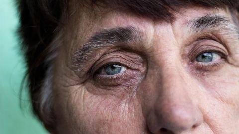 Sehen im Alter: Eine ältere Frau guckt an der Kamera vorbei in die Ferne.