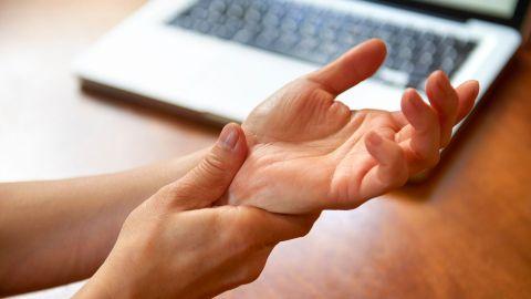 Sehnenscheidenentzündung: Eine Frau sitzt an einem Schreibtisch, auf dem ein Laptop steht, sie ist offenbar arbeiten. Mit der rechten Hand fasst sich die Frau an das Handgelenk der anderen Hand. Dabei presst sie ihren Daumen auf die Handwurzel.