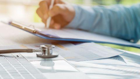 Patientenquittung: Ein Laptop und ein Stethoskop liegen auf einem Schreibtisch. Am gleichen Tisch sitzt ein Arzt. Er schreibt mit einem Kugelschreiber auf ein Blatt Papier, das auf einem Klemmbrett fixiert ist.