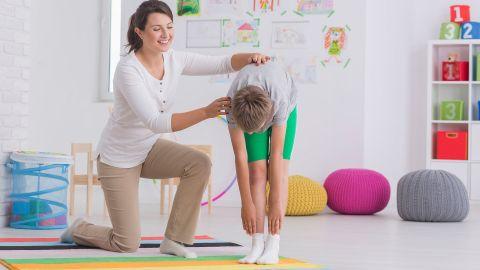 Eine lächelnde Physiotherapeutin stützt einen Jungen, der sich stehend nach vorne beugt und versucht, mit den Händen seine Füße zu berühren.