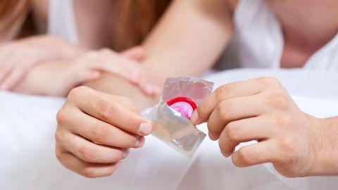 STI: Ein Mann öffnet eine silberne Kondomverpackung. In der Verpackung steckt ein rotes Kondom.