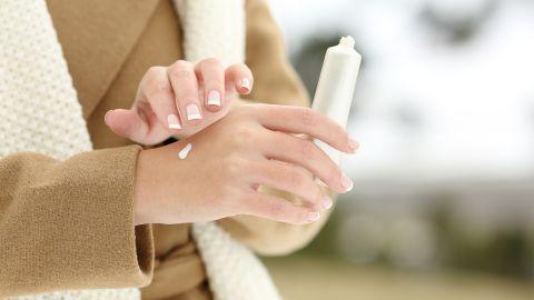 Trockene Haut: Eine Frau trägt einen Wintermantel. Sie hält eine weiße Creme in der Hand. Mit der einen Hand trägt sie die feuchtigkeitsspendende Creme auf die andere Hand auf.