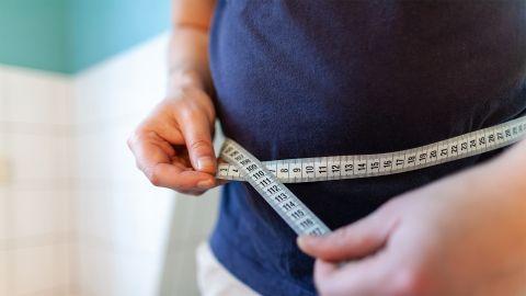 Übergewicht: Ein Mann misst seinen Bauchumfang mit einem Maßband, das er mit beiden Händen vor dem Bauch zusammenhält.