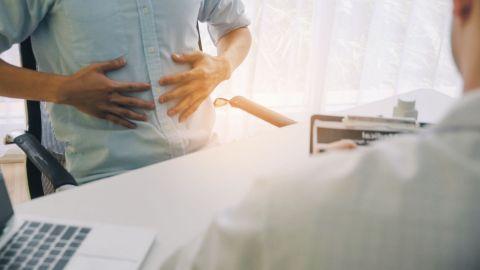 Ein Mann sitzt in einem Behandlungszimmer vor einem Arzt und fasst sich mit beiden Händen an den Bauch. Der Arzt hält einen Auswertungsbogen in der Hand.