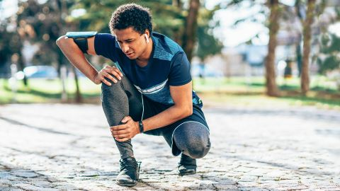 Vorderer Knieschmerz: Ein junger Mann in Sportkleidung kniet im Freien. Er hält sich das Knie und verzieht das Gesicht. Er scheint sein Lauftraining aufgrund von Schmerzen unterbrochen zu haben.