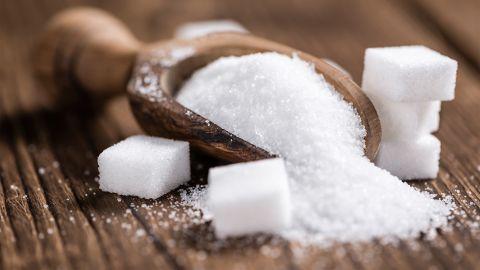 Zucker: Eine Holzschaufel ist mit Zuckerkristallen befüllt. Rechts und links neben der Schaufel liegen mehrere Zuckerwürfel