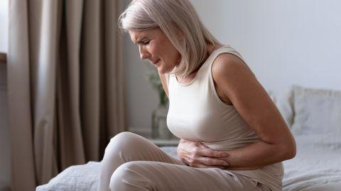 Zwölffingerdarmgeschwür: Eine ältere Frau sitzt auf dem Bett. Sie hält sich den Bauch und zieht die Beine an, ihr Gesicht ist schmerzverzerrt.